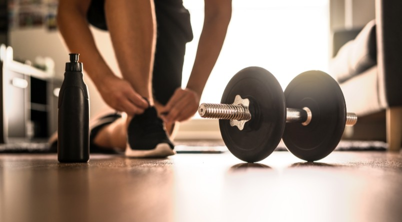 Person tying sneakers before performing an at home workout with dumbbells