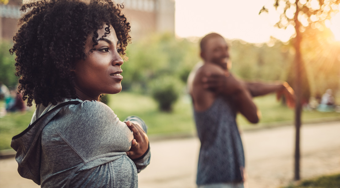 African american couple stretching arms and shoulders outdoors