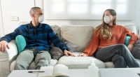 Couple social distancing and wearing face mask in the living room couch during covid-19 pandemic