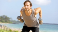 Man performing two handed dumbbell row on the beach