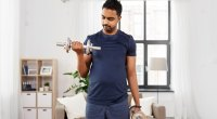 Indian-Man-Performing-Bicep-Curls-Exercise-at-Home-Living-Room