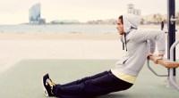 Male wearing hoodie sweatshirt doing dips exercise outside