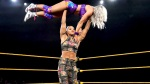 WWE pro-wrestler Bianca Belair performing overhead press with another wrestler