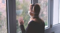 Woman wearing Coronvirus-Face-Mask Looking Out The Window
