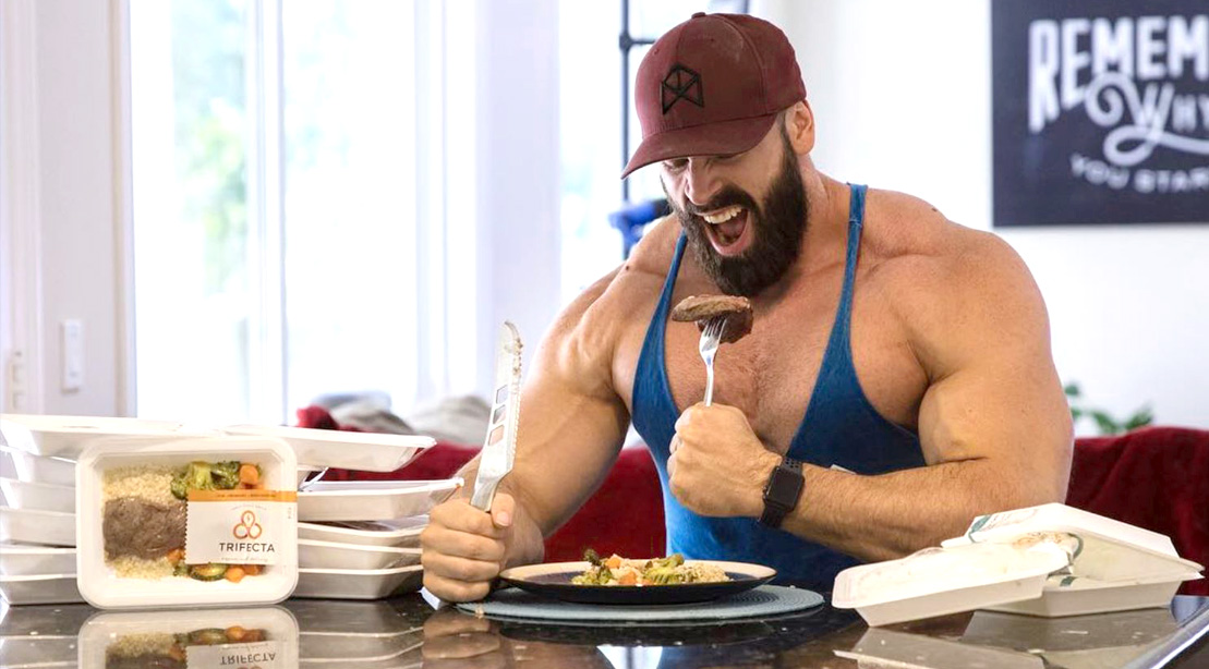Bodybuilder eating a Trifecta meal in the kitchen