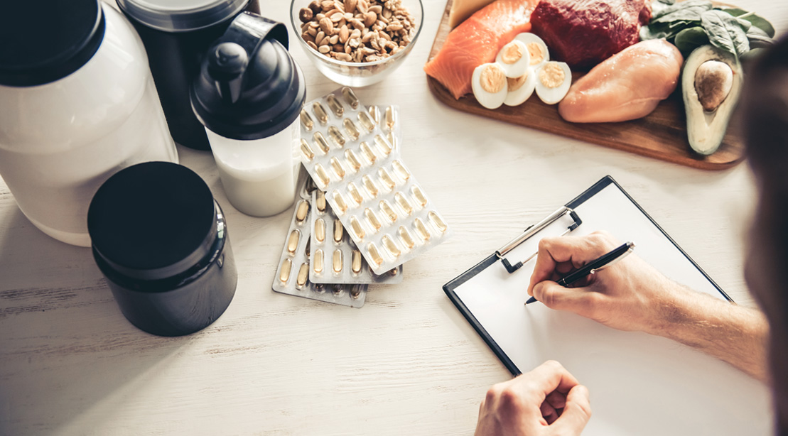 Bodybuilder writing a meal plan with supplements and food ingredients on the table