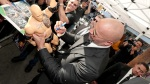 Dwayne The Rock Johnson signs a fan WWE action figure at a red carpet event