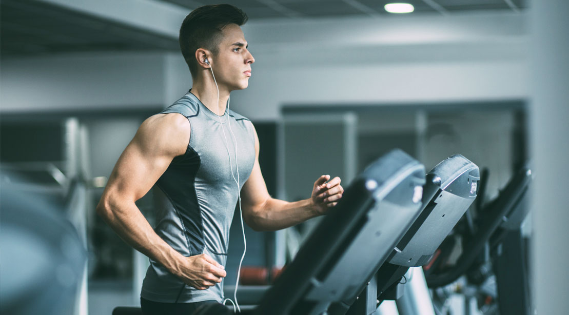 Focused and fit man running on a treadmill and learning how to run