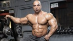 IFBB Pro-bodybuilder Jon DeLarosa in the gym standing next to a barbell rack