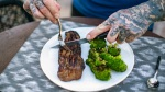 Jim Stoppani cutting a steak on a plate and broccoli