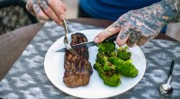Jim Stoppani cutting a steak on a plate and broccoli