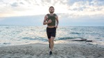 Man running on the beach while wearing a weighted vest