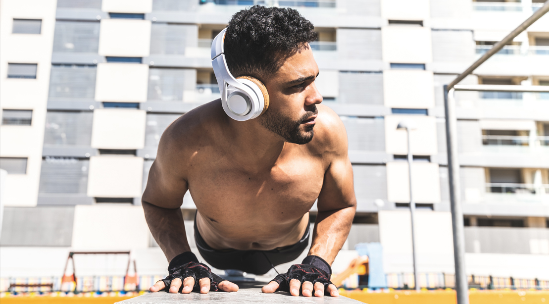 Fit male wearing headphones while doing pushup exercise in an apartment complex