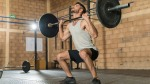 Skinny young man doing barbell squat exercise