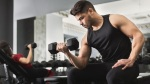 Young man working out biceps with dumbbell curl exercise