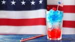 A red white and blue cocktail in front of the American Flag