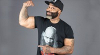 Bodybuilder C.T. Fletcher pointing to his biceps