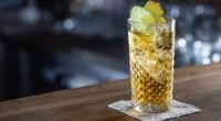 Burbon ginger lemonade cocktail garnished with lime and candied ginger