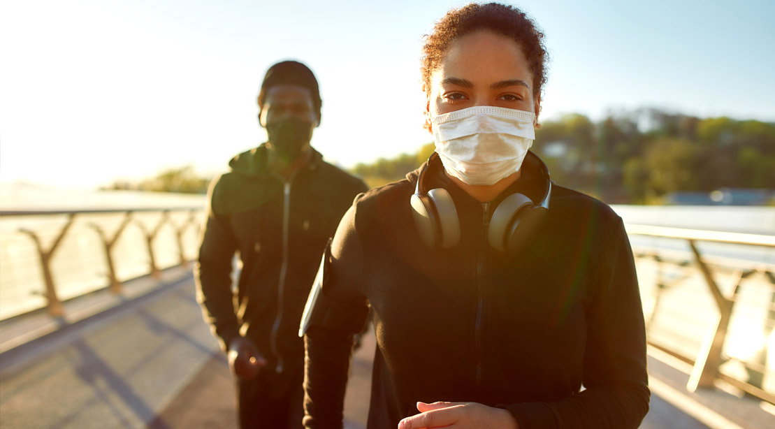 Couple running outdoors while wearing a face mask during the Covid-19 Pandemic