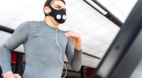 Fit man running on a treadmill while wearing a high altitude training mask