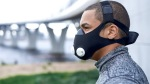 Fit man training outdoors while wearing a high altitude training mask
