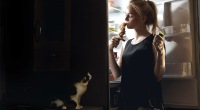 Girl eating chicken drumstick from the fridge while cat watches