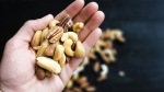 A variety of nuts in the palm of a hand.
