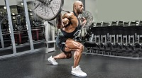 Professional bodybuilder Juan Morel performing a barbell lunge stance squat exercise
