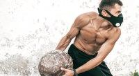 Muscular man doing medicine ball workout wearing a training mask