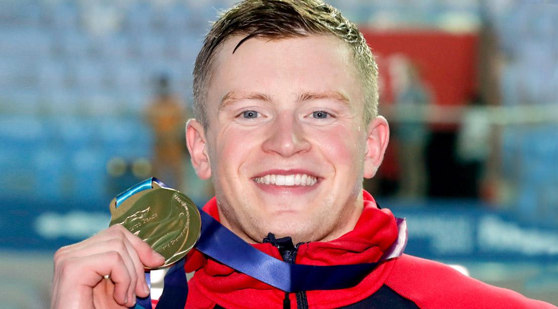 2016 Olympic gold medal breaststroke swimmer winner Adam Peaty holding his medal