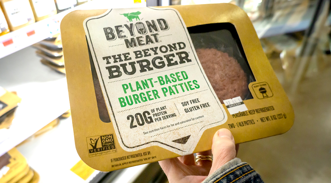 Person grocery shopping for Beyond Meat Beyond Burger