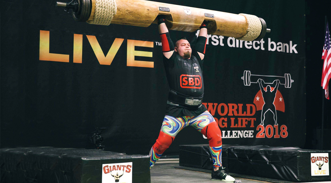 Strongman Rob Kearney lifting a heavy log at a strong man competition