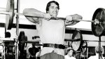 Arnold Schwarzeneggar working out doing an upright barbell row exercise