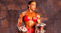 Pro female bodybuilder and former Ms. Olympia Lenda Murray holding barbells in a red bikini