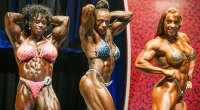 Former Ms. Olympia Iris Kyle and Dayana Cadeau posing in a female bodybuilding competition