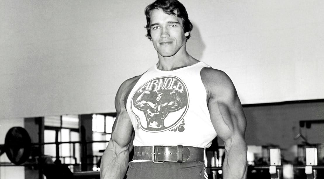 Bodybuilder and former governor of California Arnold Schwarzeneggar smiling in the gym