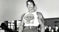 Bodybuilder and former governor of California Arnold Schwarzeneggar smiling in the gym