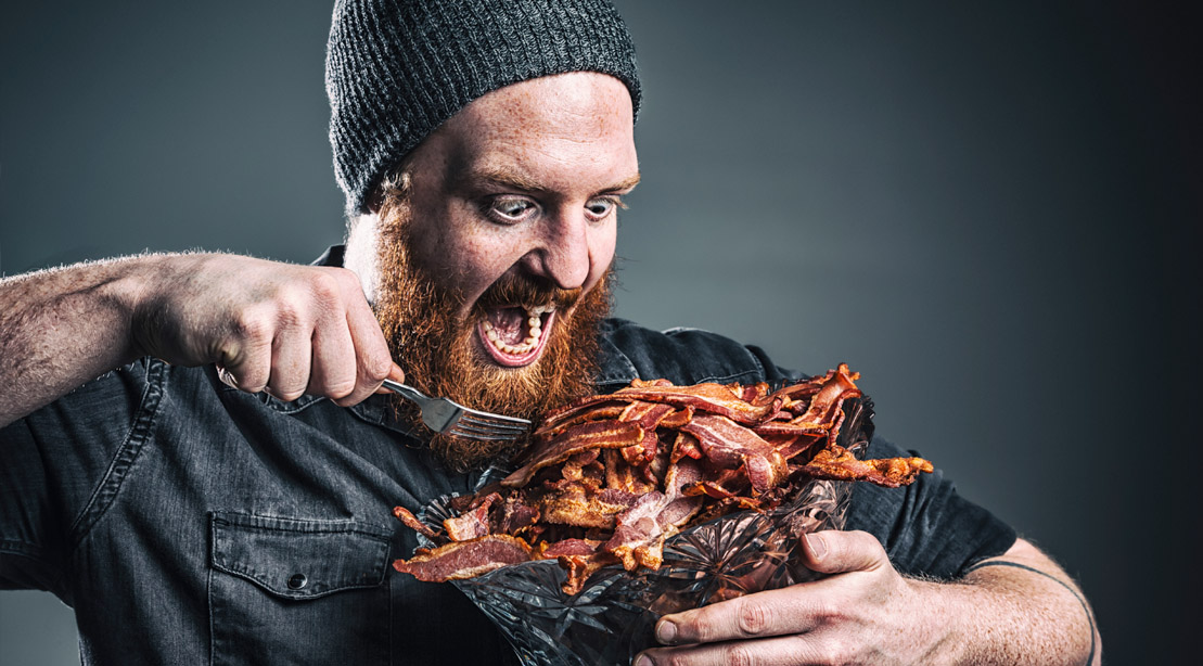 Hungry bearded man eating a bucket of bacon on the keto diet