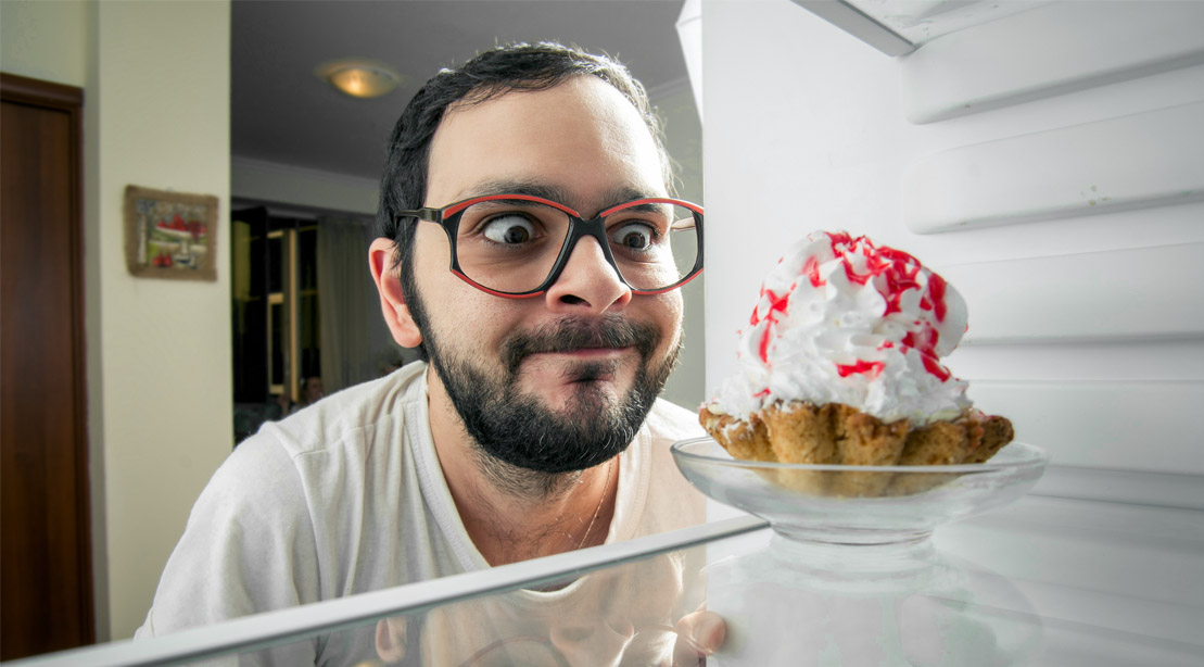 Hungry overweight man on a diets looking at a cupcake in his refrigerator