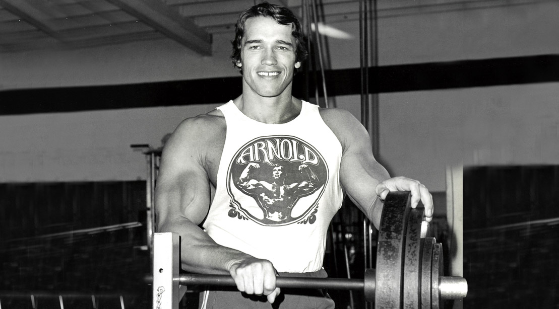 Young Arnold Schwarzenegger standing behind a barbell bench after working out