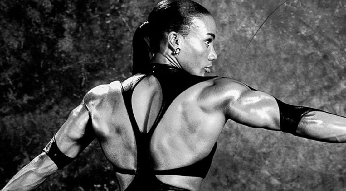 Bodybuilding woman Lenda Murray posing with motorcycle