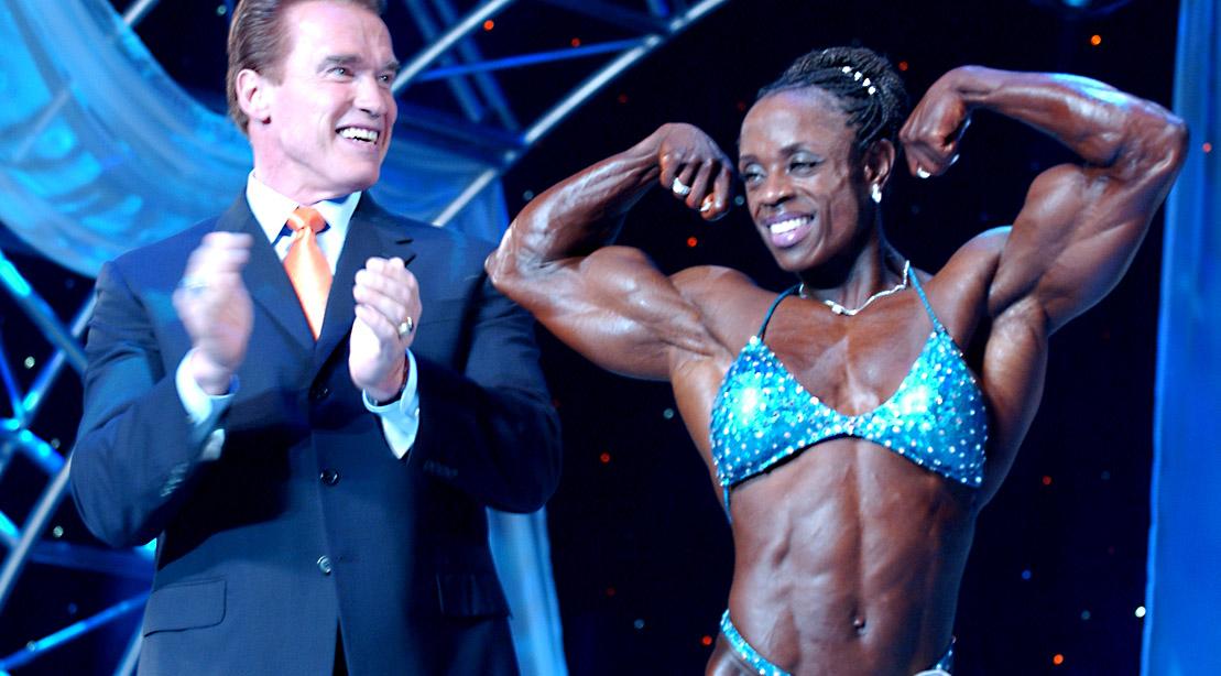 Ms. Olympia and professional female bodybuilder Iris Kyle posing next to Arnold Schwarzenegger