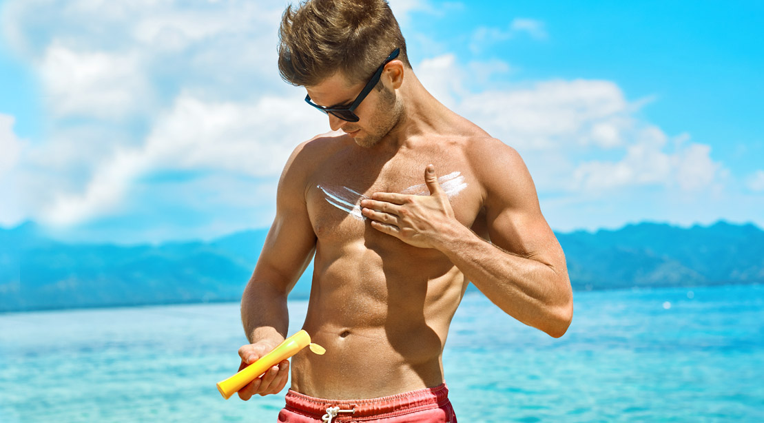 Muscular-Man-Applying-Sunscreen-To-His-Chest