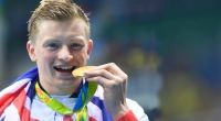 Olympic gold medal swimmer Adam Peaty biting his gold medal