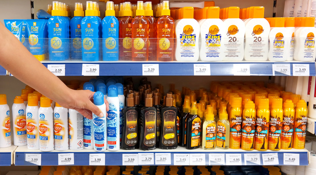 Person shopping for sunscreen in the sunscreen aisle of the supermarket