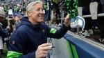 Seattle Sea Hawks Head Coach Pete Carroll autographs a fan's necklace after a football game