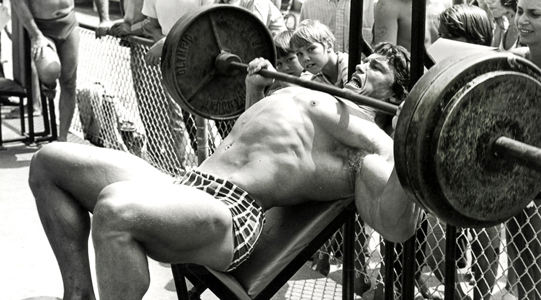 Bodybuilder Arnold Schwarzenegger working out outdoors at Venice Beach with a barbell bench press exercise