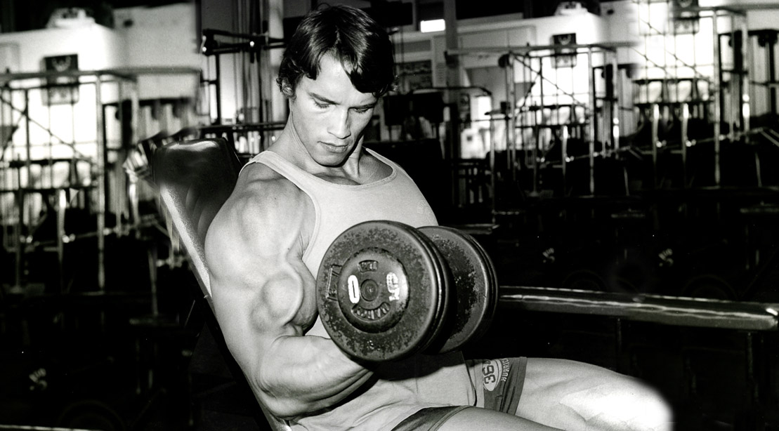 Young Arnold Schwarzenegger working out his biceps and arms with a dumbbell bicep curl