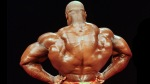 Legendary bodybuilder Ronnie Coleman flexing his middle back muscles and showing his back muscle definition