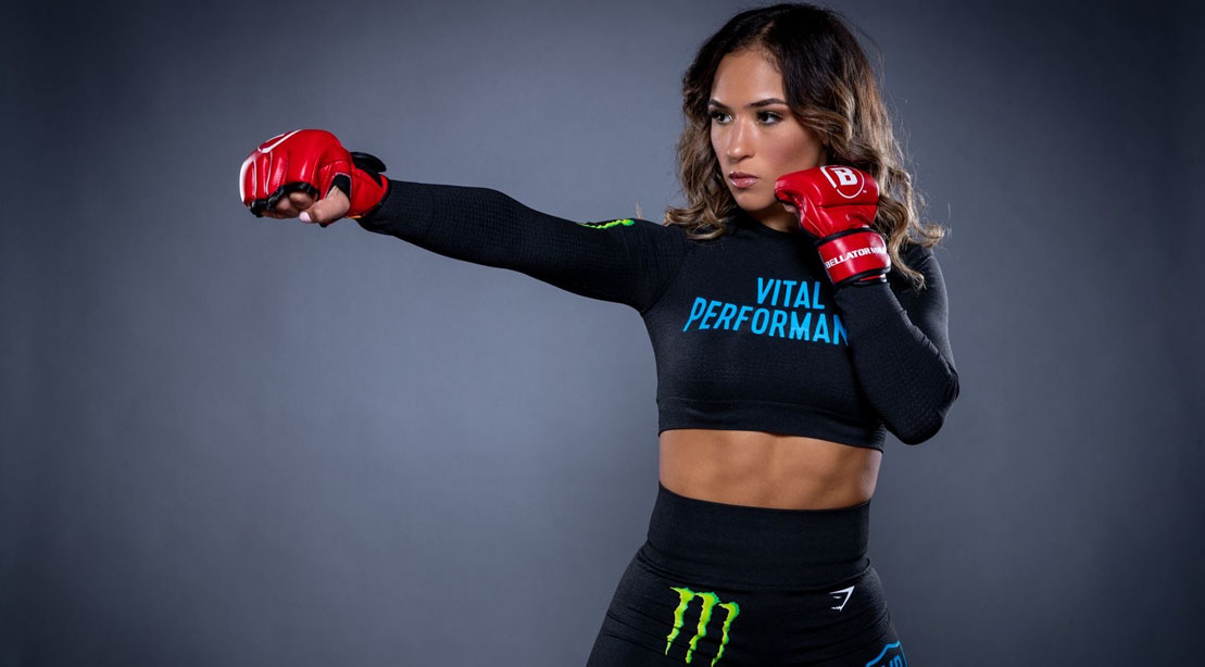 Female MMA fighter Valerie Loureda wearing a vital performance shirt and throwing a right jab